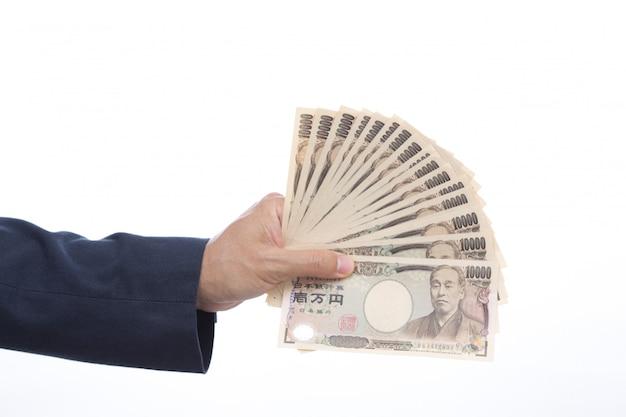 Mano que sostiene el billete de banco japonés en el fondo blanco. dinero japonés