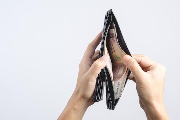 Mano que sostiene la billetera de cuero de hombre llena con billetes tailandeses de 1000 baht