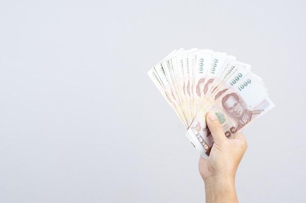 Mano que sostiene los billetes de banco tailandeses de 1000 baht o dinero moneda en tailandia