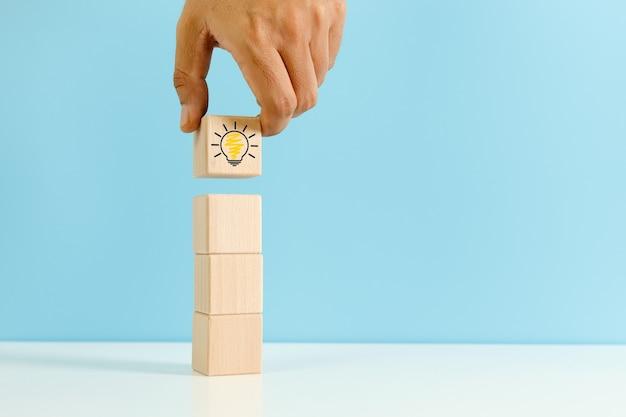 Mano que sostiene el bloque del cubo de madera con fondo azul del icono de la bombilla. símbolo de creatividad, ideas y conceptos creativos. copie el espacio.
