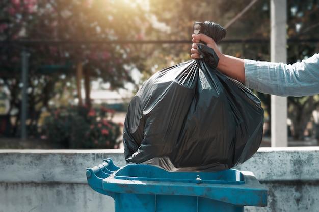 Mano que sostiene la bolsa de basura negro poniendo en la basura