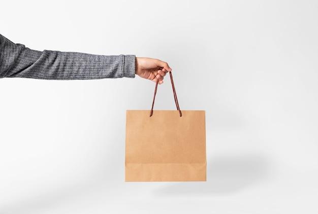 Mano que sostiene la bolsa de papel marrón en blanco para la publicidad de la plantilla de la maqueta y que califica en fondo gris.