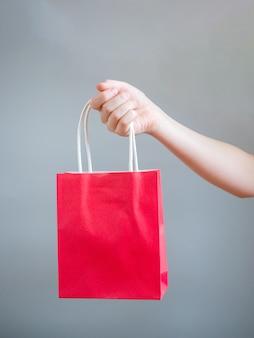 Mano que sostiene el bolso rojo para la plantilla en blanco maqueta aislada sobre fondo gris