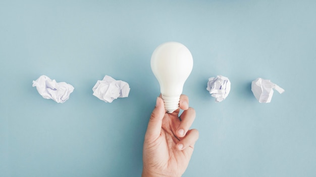 Mano que sostiene la bombilla de luz blanca con bolas de papel arrugado sobre fondo gris