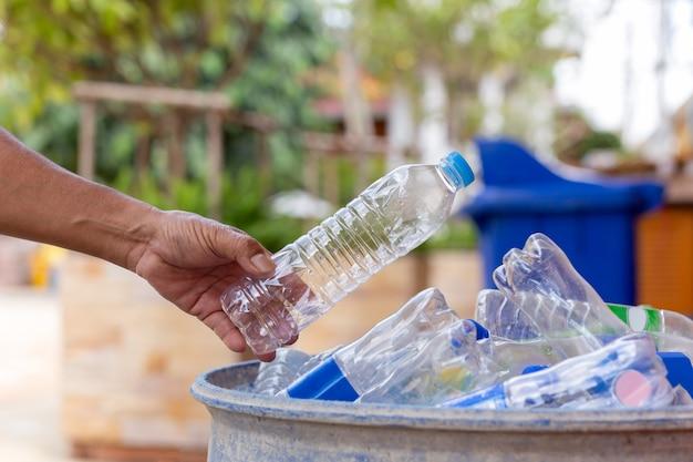 Mano que sostiene la botella de plástico reciclable en el contenedor de basura para la limpieza.