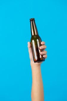 Mano que sostiene la botella usada sobre fondo azul.