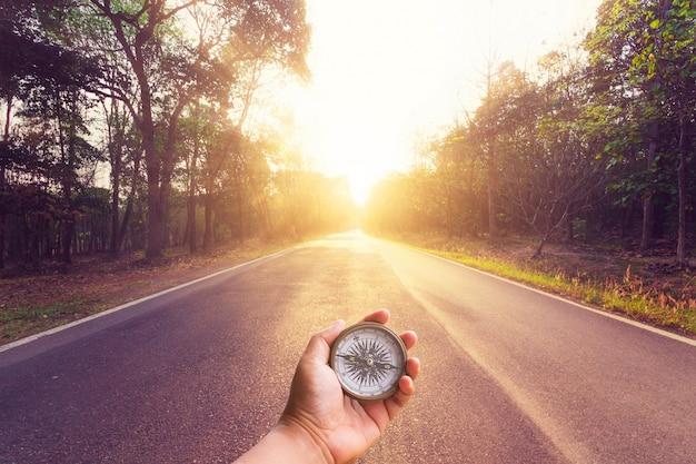 Mano que sostiene la brújula en la carretera de asfalto vacía y la puesta del sol.