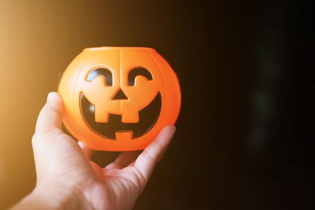 Mano que sostiene la cabeza de calabaza de halloween con luz dorada en la noche oscura bakckground. concepto de fiesta de halloween.