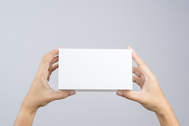 La mano que sostiene la caja blanca en blanco da el regalo