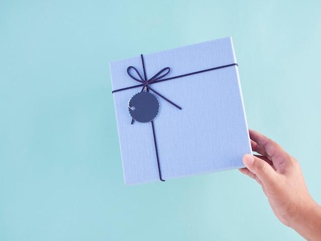 Mano que sostiene la caja de regalo azul.