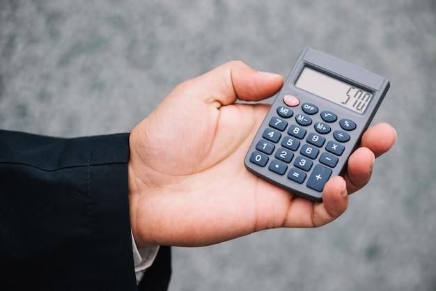 Mano que sostiene la calculadora con resultado calculado