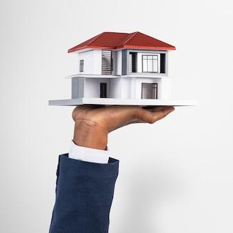 Mano que sostiene la casa modelo de bienes raíces y propiedad