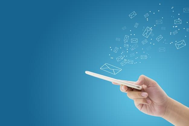 Mano que sostiene el cheque del hombre y el envío de mensajes con el correo electrónico en un teléfono sobre fondo azul.