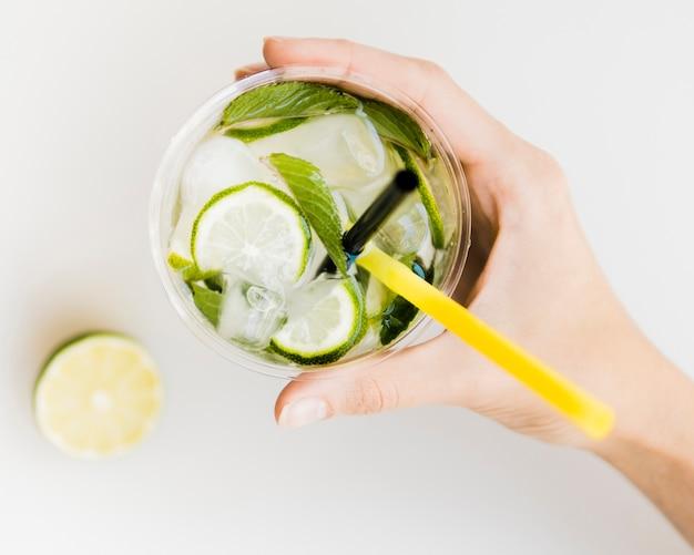 Mano que sostiene el cóctel frío con menta, limón y hielo