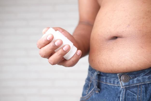 Mano que sostiene el contenedor de píldoras médicas y el concepto de sobrepeso de grasa abdominal