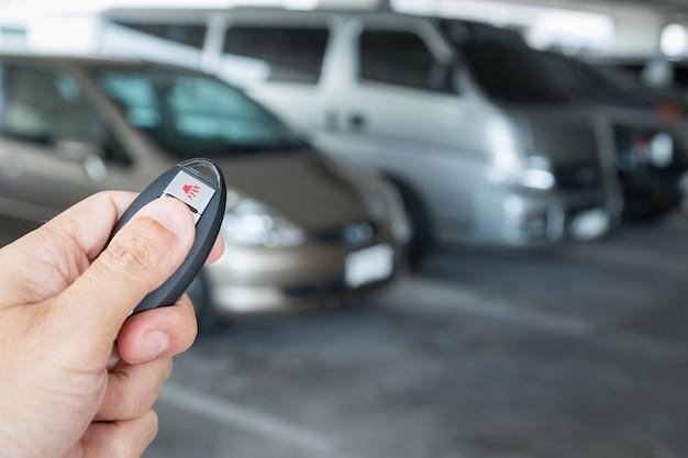 Mano que sostiene el control remoto de la llave del coche en el fondo del aparcamiento