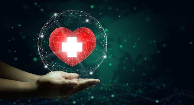 Mano que sostiene el corazón rojo con el símbolo de la cruz blanca concepto de caridad de seguro de salud de atención médica