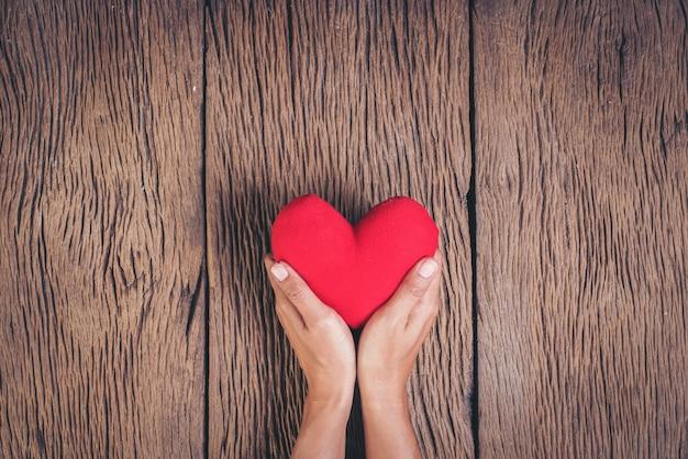 Mano que sostiene el corazón rojo sobre fondo de madera