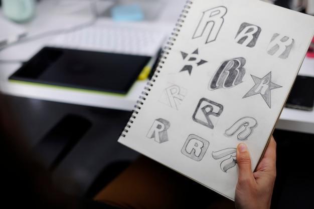 Mano que sostiene el cuaderno con drew brand logo ideas de diseño creativo