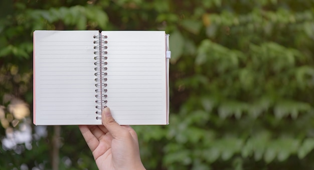 Mano que sostiene el cuaderno en el fondo del campo de hierba enfoque selectivo