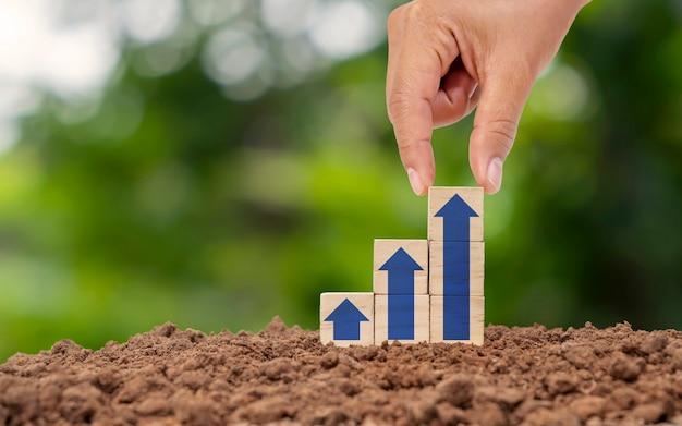 Mano que sostiene el cubo de madera con el icono de la flecha que se eleva continuamente en el concepto de crecimiento financiero y empresarial del suelo