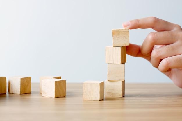 Mano que sostiene los cubos de madera en blanco en la mesa de madera sobre blanco