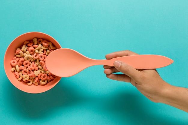 Mano que sostiene la cuchara cerca de la taza con letras del alfabeto comestible