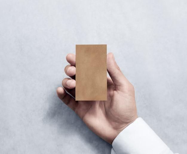 Mano que sostiene el diseño vertical en blanco de la tarjeta de visita de kraft.