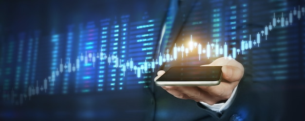 Mano que sostiene el dispositivo de teléfono inteligente y la pantalla táctil. concepto de mercado de valores. comerciante empresario mirando con velas de análisis de gráficos