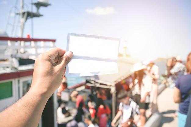 Mano que sostiene dos entradas con multitud de pasajeros anónimos en el barco.