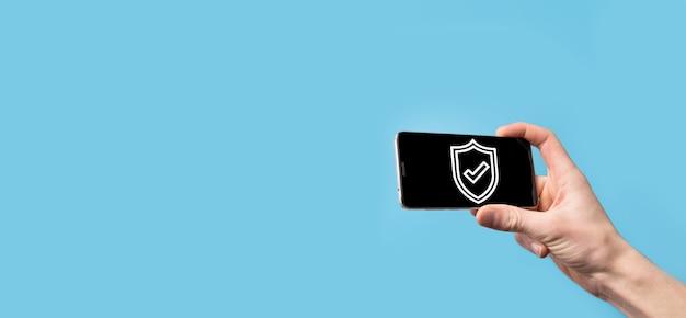 Mano que sostiene el escudo de protección con un icono de marca de verificación sobre fondo azul. seguridad de la red de protección