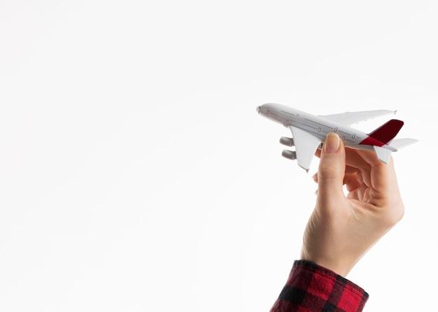 Mano que sostiene la figurilla de avión con espacio de copia
