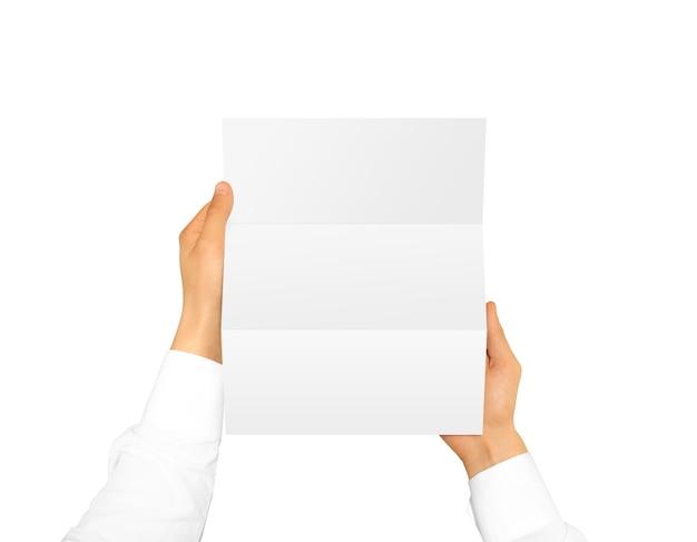Mano que sostiene el folleto folleto en blanco en la maqueta de la mano