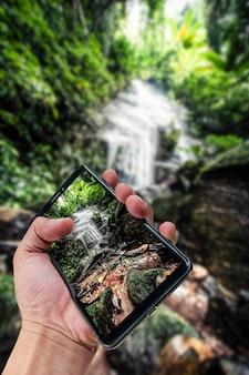 Mano que sostiene el fondo de la naturaleza del paisaje del smartphone