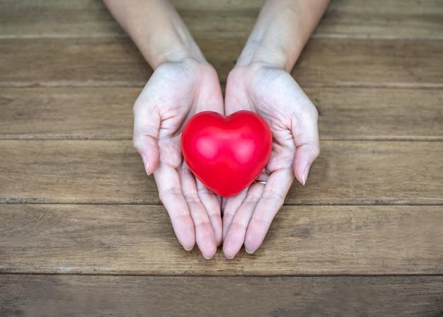 Mano que sostiene la forma del corazón en la mesa de madera
