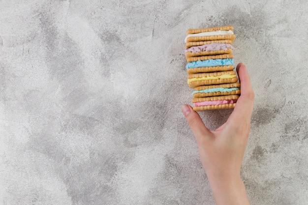 Mano que sostiene las galletas sabrosas en fondo gris