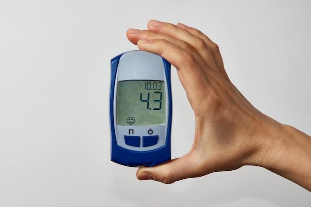 Mano que sostiene el glucómetro con resultado de la prueba de azúcar en sangre. mano de mujer mostrando prueba de azúcar, sobre fondo blanco con espacio de copia, primer plano.