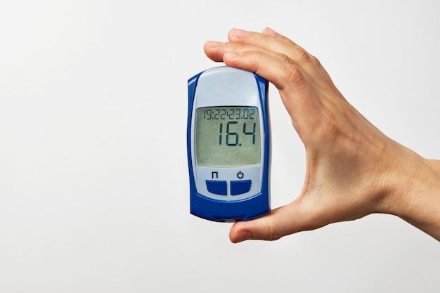 Mano que sostiene el glucómetro con resultado de la prueba de azúcar en sangre. mano de mujer mostrando prueba de azúcar, sobre fondo blanco con espacio de copia