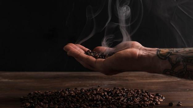 Mano que sostiene los granos de café caliente