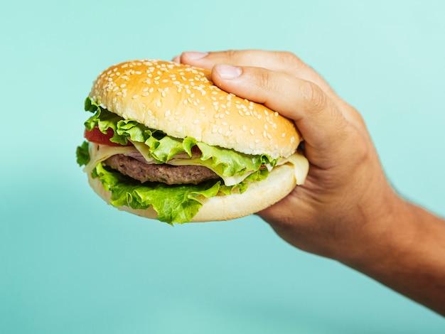 Mano que sostiene la hamburguesa deliciosa con fondo azul