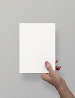 Mano que sostiene la hoja de papel a5