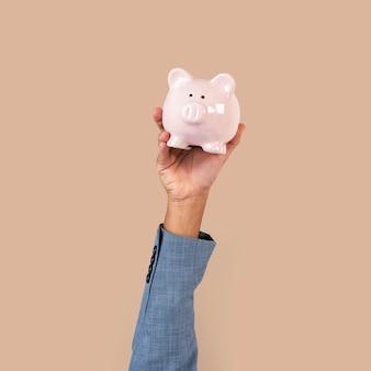 Mano que sostiene la hucha en concepto de finanzas