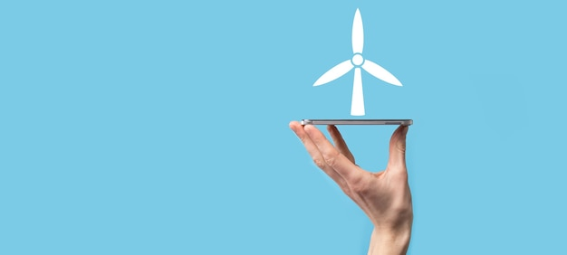 Mano que sostiene un icono de un molino de viento que produce energía ambiental sobre fondo azul.