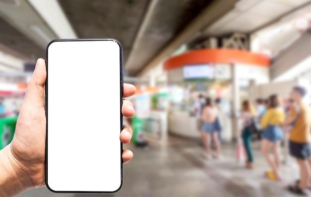 Mano que sostiene las imágenes borrosas del teléfono inteligente toque de desenfoque abstracto del pasajero de la gente pararse en la cola de la línea y esperar la puerta de entrada automatizada para el tren en la estación de tren del cielo desenfoque de fondo.