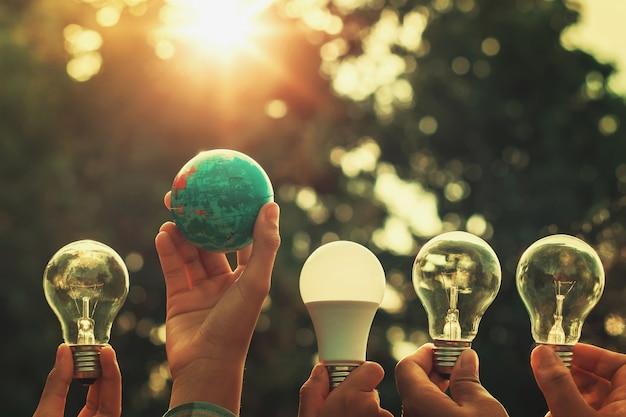 Mano que sostiene el juguete de la bombilla y del mundo con puesta del sol. concepto de poder energético en la naturaleza