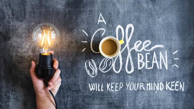Mano que sostiene la bombilla iluminada con café sobre el texto en la pizarra
