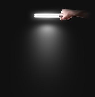 Mano que sostiene la lámpara cerca de la pared, aislada