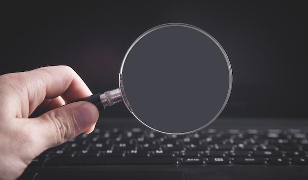 Mano que sostiene la lupa con el teclado de la computadora portátil. buscando en internet