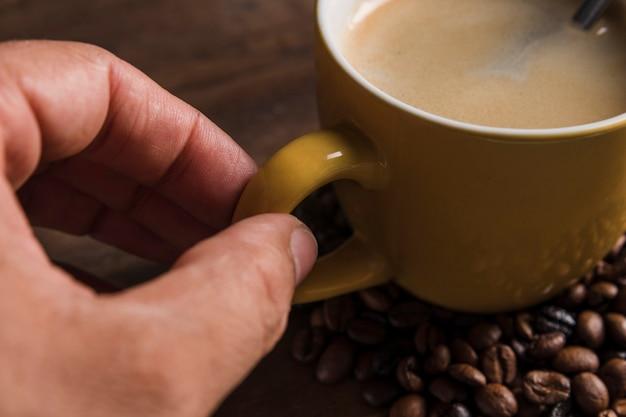 Mano que sostiene la manija de la taza con café