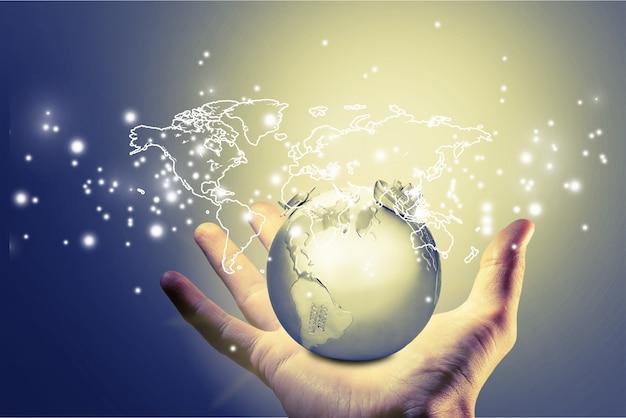 Mano que sostiene el mapa del mundo digital brillante y el globo terráqueo en el fondo